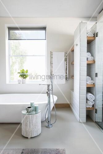 Free-standing bathtub below window and next to masonry shelving