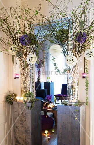 Elegant arrangements of artificial flowers, fairy lights and glass vases on grey plinths in front of living area