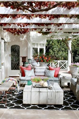 Autumnal seating area below vine-covered pergola