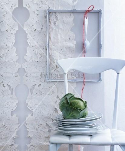 Weißer Stuhl mit Tellerstapel und Kohlkopf vor dekorierter Wand