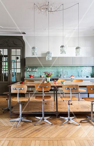Alte Drehstühle um einen großen Arbeitstisch in der Küche – Bild ...