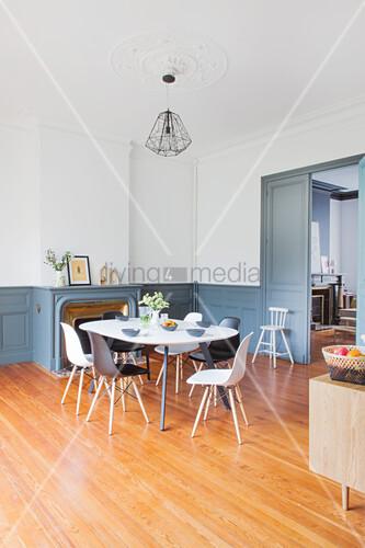 Esstisch mit Stühlen vor Kamin im Wohnraum mit weissen Wänden und grau-blauer Vertäfelung im Sockelbereich