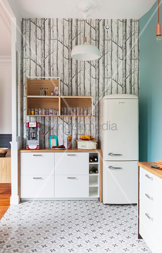 White base units and fridge against tree-patterned wallpaper in kitchen with patterned cement floor tiles
