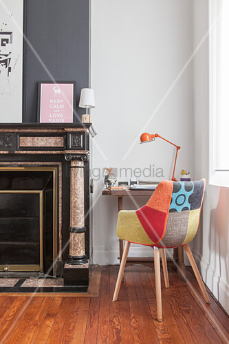 Retro armchair and small desk next to fireplace in living room in shades of grey