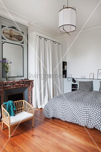 Doppelbett mit gepunkteter Bettwäsche, Umkleidekabine mit Vorhang und Kamin im Schlafzimmer