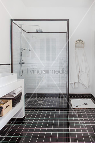 Shower cubicle with glass walls in black and white bathroom