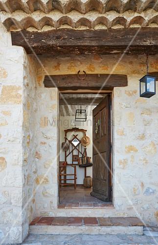 Open wooden front door of rustic stone house