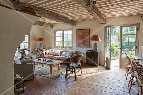 Wood-beamed ceiling, tiled floor and terrace doors in rustic living room