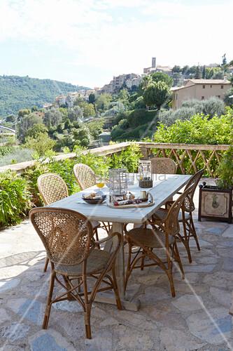 Holztisch mit Armlehnstühlen auf der Dachterrasse mit Natursteinboden