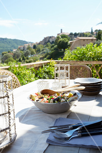 Bowl of salad, cutlery and plates on table on roof terrace