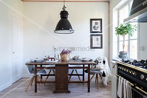 Alter Holztisch mit modernen Stühlen in der Küche mit Gasherd – Bild ...