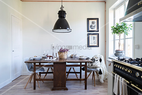 Old wooden table, modern chairs and gas cooker in kitchen