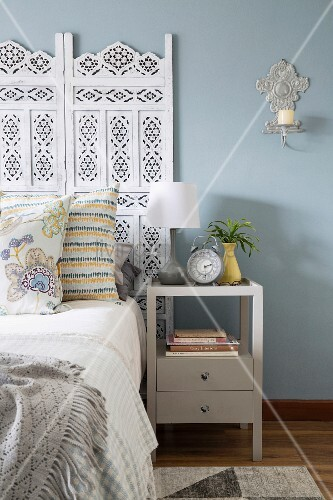 Bedside cabinet next to double bed with ornate headboard