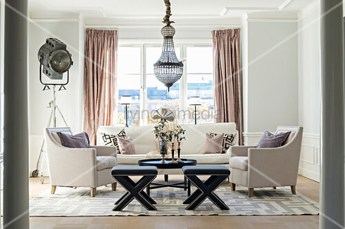 Elegant living room with pale sofa set and chandelier