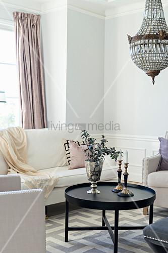 Pale sofa set and chandelier in elegant living room
