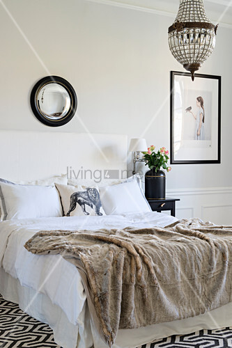Fur blanket on bed in elegant black and white bedroom