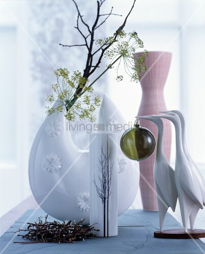 Crane figurines in front of branches and various vases