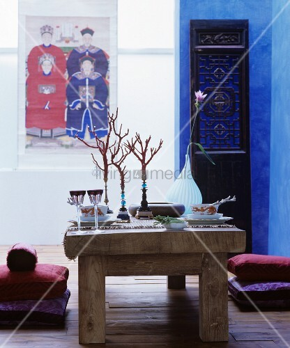 Rustic wooden table set in Oriental style and floor cushions