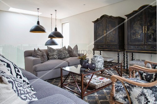 Upholstered furniture and antique ethnic artworks in stylish lounge area