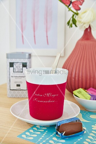 A mug of tea and a piece of chocolate in front of a vase with flowers