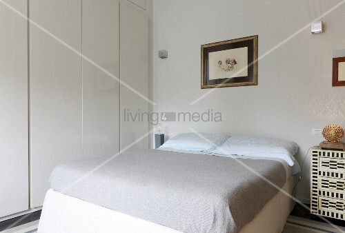 Double bed, hand-crafted bedside cabinet and white fitted cupboards in bedroom