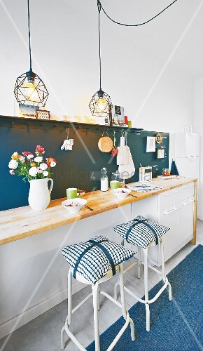 A breakfast bar with flowers in a vase, pendant lights and bar stools with cushions