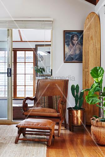 Vintage Ledersessel mit Fußhocker neben Zimmerpflanzen und Surfbrett in Zimmerecke