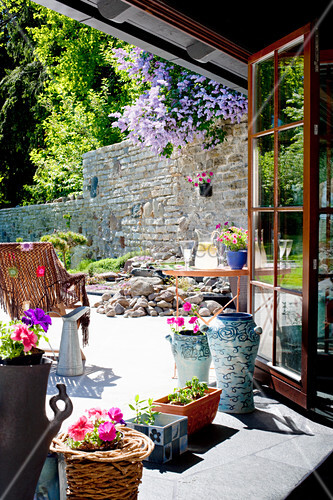 Flowers on windowsill with view of terrace with stone back wall