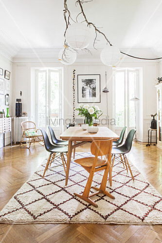 Bright dining room in natural shades in period apartment with floor-to-ceiling windows