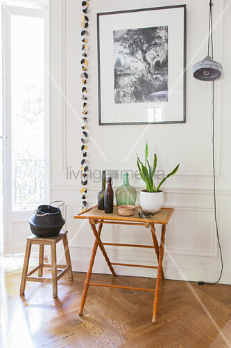 Folding table and stool against panelled wall
