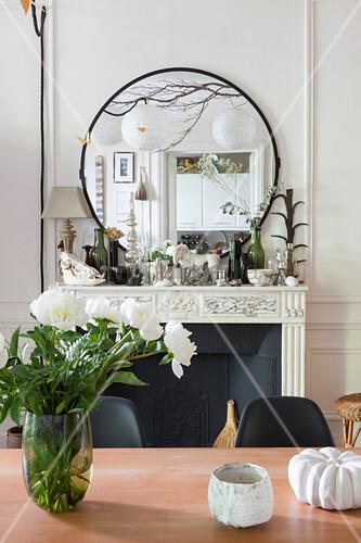 Blumenstrauß auf dem Esstisch vor der üppig dekorierten Kaminkonsole
