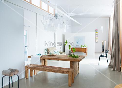 Modernes Esszimmer im Loft mit Betonboden und Holzmöbeln