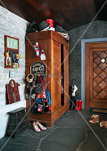 Garderobe an einem alten Schrank im Eingangsbereich mit Steinboden