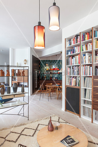 View past bookcase in living room into open-plan kitchen