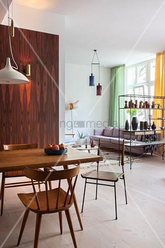 Blick vom Esszimmer mit Holzmöbeln und Holzwand ins Wohnzimmer