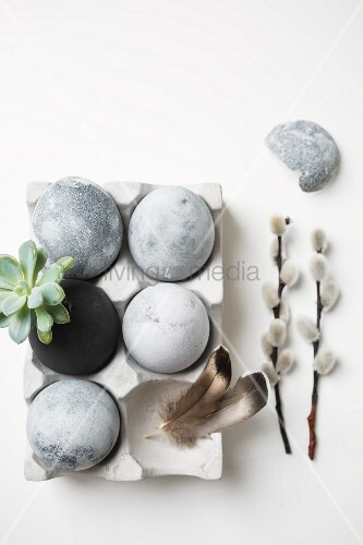 Easter eggs painted with stone effects in concrete egg box