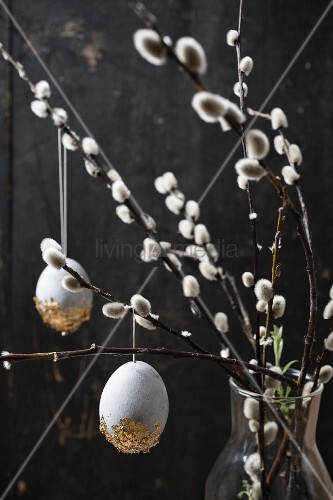 Easter eggs painted with stone effects and gold leaf hung from willow branches