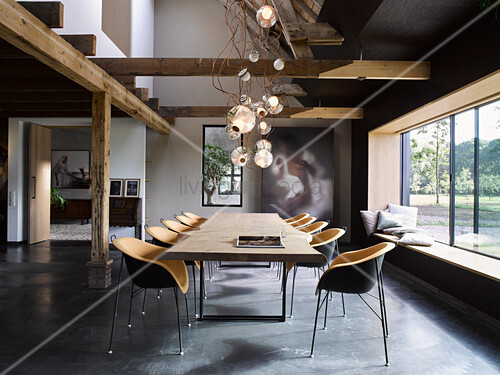Custom-made dining table and designer chairs next to huge window in open-plan interior