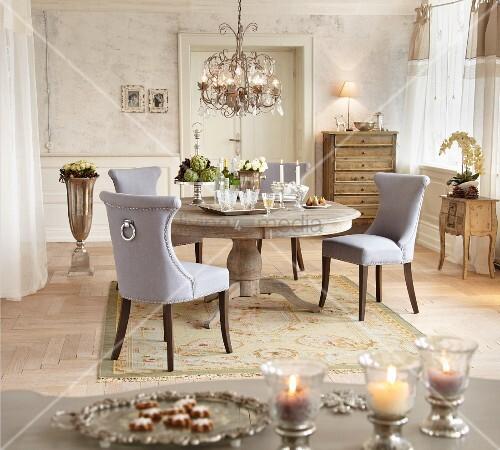 Graue Polsterstühle um rustikalen runden Tisch mit Silbertablett und Kronleuchter in Altbauwohnung