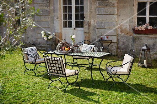 Metal furniture in sunny garden outside country house