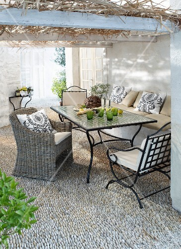 Comfortable seating area on gravel terrace below roofed pergola
