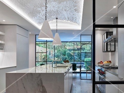 Glass and steel partition wall and marble island counter in modern kitchen