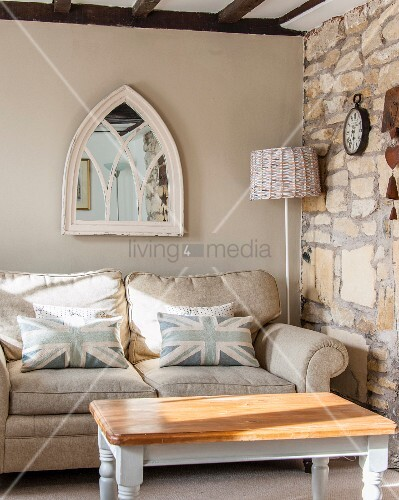 Mirror in window frame above sofa with Union-flag scatter cushions