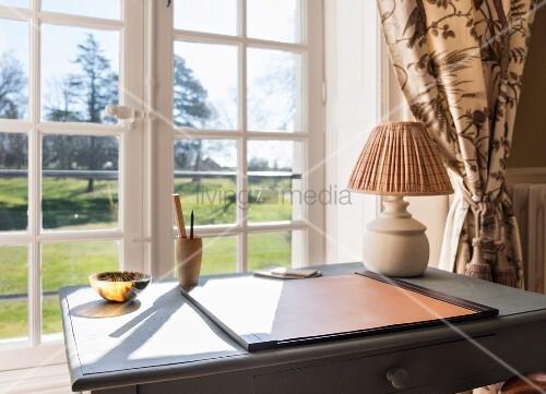Blick über den Schreibtisch durchs Fenster auf den Garten