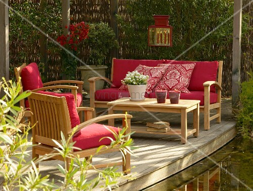 Outdoor furniture with red cushions on wooden terrace next to garden pond