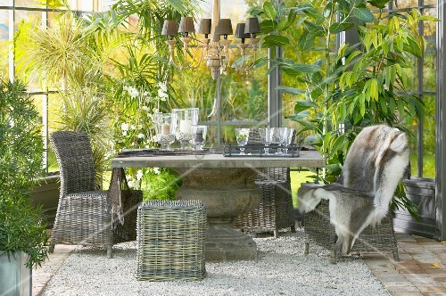 Rattan chairs around solid stone table on gravel floor in conservatory