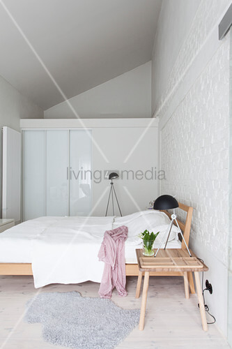 Simple wooden furniture in bedroom with white-painted brick wall