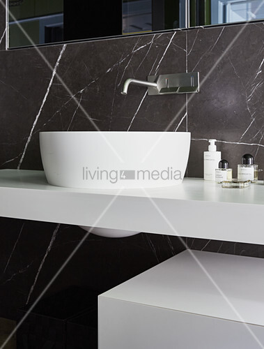 Modern sink and black marble wall in bathroom