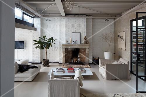 Loft-Wohnzimmer in Schlammtönen, Sitzmöbel und Couchtisch vor Kamin