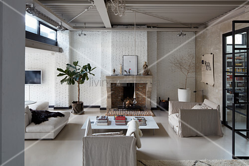 Seating and coffee table in front of fireplace in loft-apartment living room in natural shades